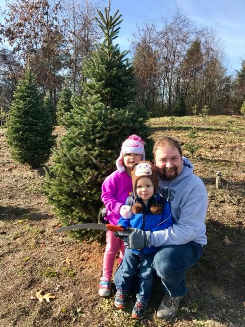 Family standing next to christmas tree to cut down e1541099470730