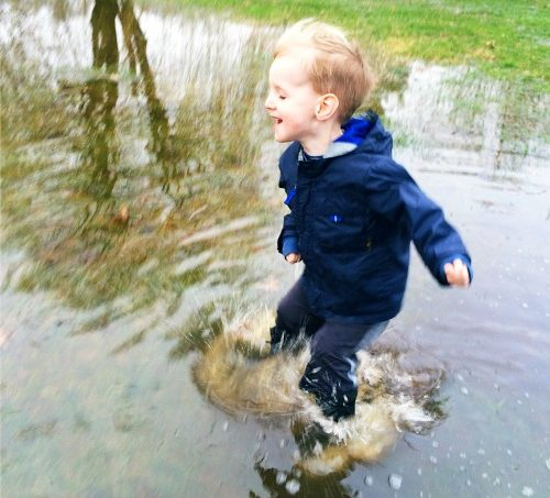 boy jumping in puddles