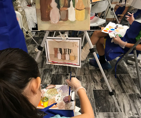 girl paints on an easel with acrylic paint