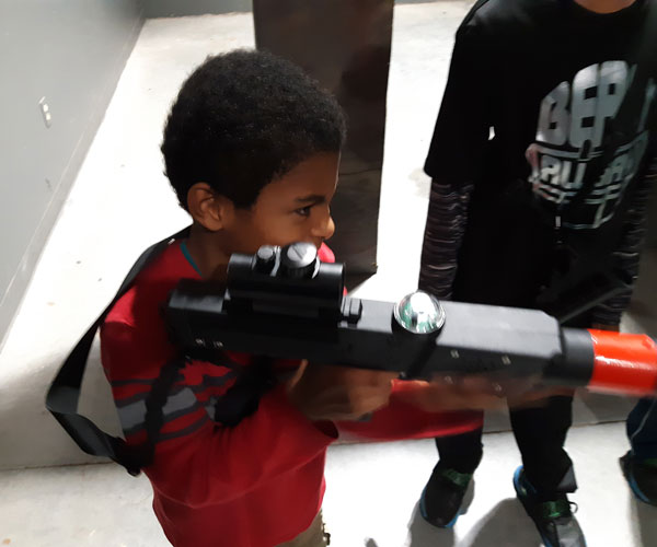 young boy holding laser tag gun and aiming