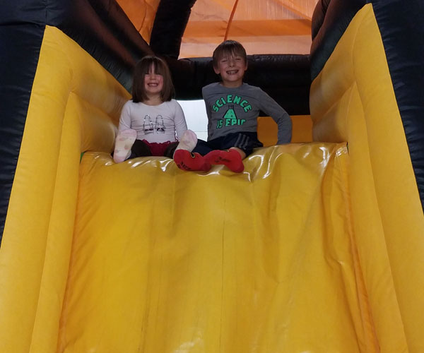 boy and girl smiling at top of inflatable slide