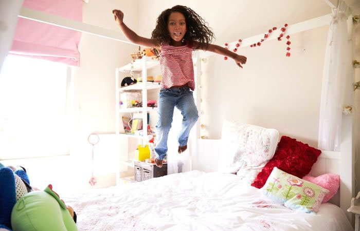 Helping Kids During Shutdown girl jumping on bed