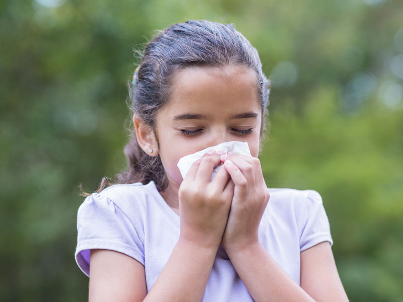 Child with allergies girl blowing her nose