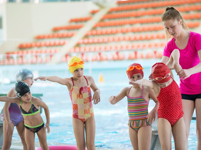 kids taking swim lessons at pool